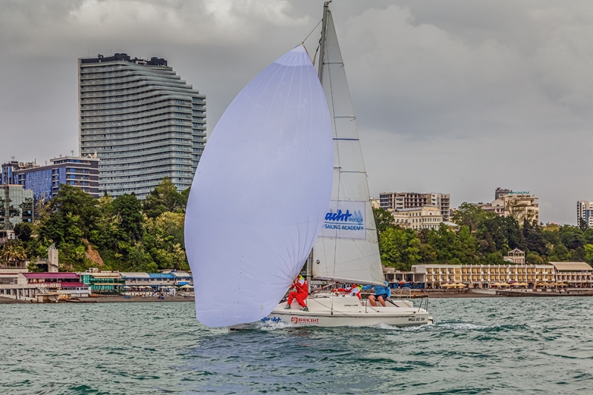 "The leading ""Elan 210"" yacht during a regatta against the background of the coast of Sochi"