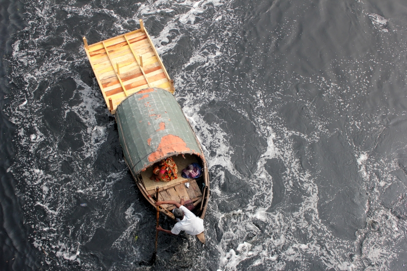 A boatman is carrying a wooden bed in front of his traditional boat