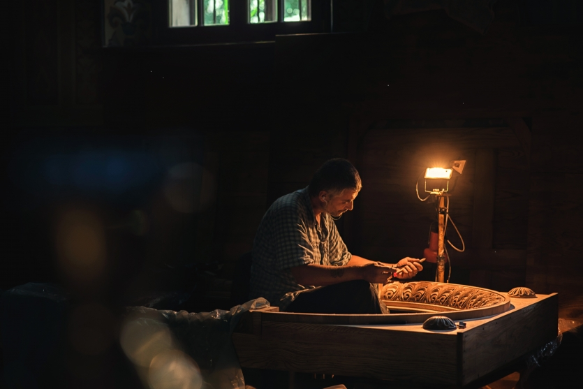 A man works in a church on a wooden iconostasis.