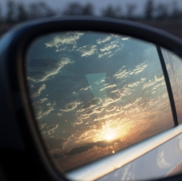 Sunset is reflected in the mirror of the car