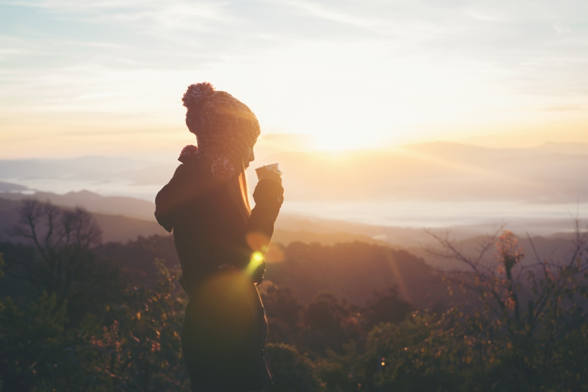 woman drink coffee at the mountain sunset