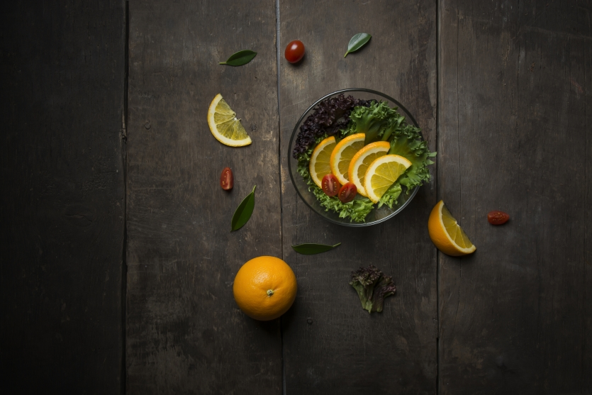 Fresh salad with slice of orange on a wooden background